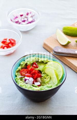 Alto ángulo de recipiente con guacamole sabroso con tomate cherry maduro y cebolla roja cerca de rodajas de lima