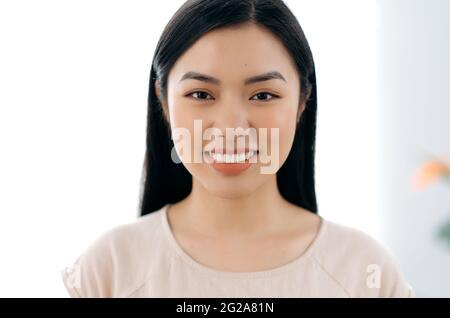 Primer plano retrato de una mujer bonita. Hermosa mujer joven de origen asiático con largo pelo morena, mirando directamente a la cámara, sonriendo amable