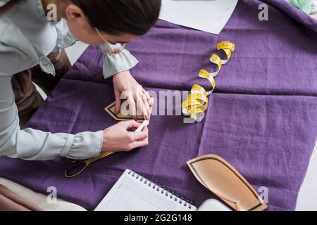 Vista superior de la tela de marcado de costurera y sujetando el patrón de costura cerca de las tijeras