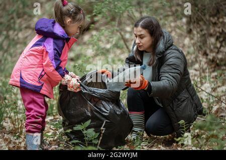 Mamá e hija limpian el bosque de plástico y otros desechos.