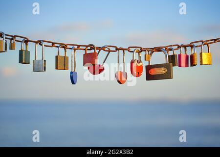 Varios y corazón de colores en forma de candados de amor en una cadena en un hermoso cielo azul y fondo del mar. Candados diversos como un símbolo de la unión y.