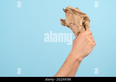 Concepto de Reciclaje y Ecología. La mano sostiene la basura de papel sobre un fondo azul.