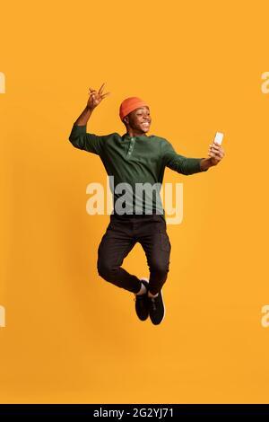 Alegre tipo afroamericano tomando selfie con smartphone mientras saltan en el aire