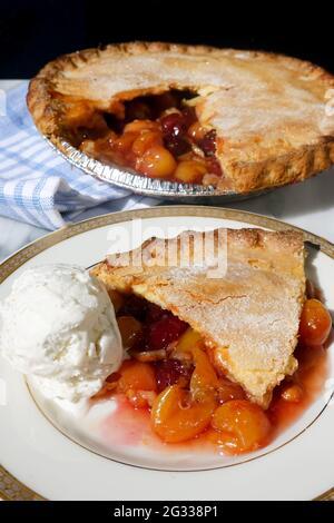 Una rebanada de pastel de cerezas removida de una tarta de cerezas caseras frescas con Rainer y cerezas rojas oscuras servidas con helado de vainilla