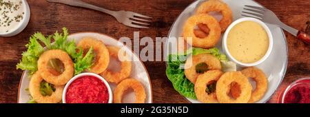 Panorama de los anillos de calamares. Anillos de calamar con vino y varias salsas, la parte superior plana rodó sobre una mesa de madera rústica oscura