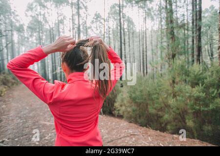 Mujer corredor que se prepara para correr tirando del pelo para hacer una cola de caballo preparándose para el sendero de larga distancia que corre en la naturaleza del bosque al aire libre. Chica atleta de