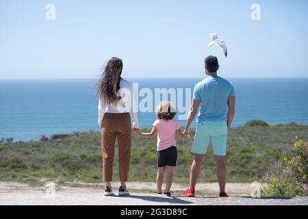 Padre, madre y niño en la playa de verano al atardecer en Hawai. Concepto de familia amigable.