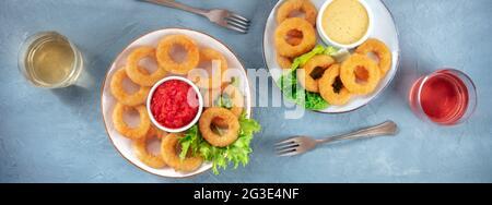 Panorama de los anillos de calamares. Anillos de calamar fritos con ensalada verde, vino y diversas salsas, top shot, flat lay