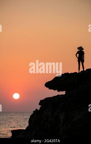Silueta de mujer joven con sombrero cónico y mirando al mar desde la cornisa de roca junto al santuario de Dinh Cao al atardecer, Duong Dong, Phu Quoc Island, K