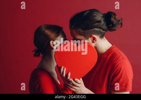 Hombre y mujer joven pareja besando y escondiéndose detrás de la caja en forma de corazón