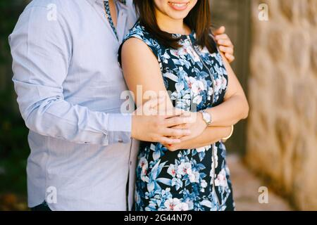 El hombre en una camisa azul abraza a una mujer sonriente en un vestido colorido