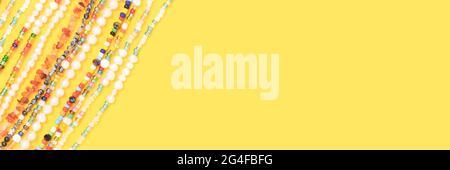 Bandera con collares hechos de cuentas y perlas sobre fondo amarillo con lugar para texto.