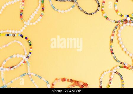 Collares y pulseras hechos de cuentas y perlas sobre un fondo dorado. Marco de borde con espacio de copia.
