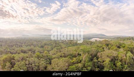 Panorama aéreo de la selva amazónica en Ecuador al atardecer con el Río Napo y la montaña Galeras en el fondo.