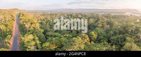 Panorama aéreo de una carretera amazónica en Ecuador con Río Napo en el fondo. Los caminos traen la colonización y la destrucción de la selva tropical al