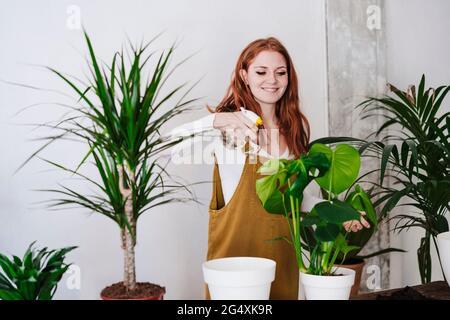 Mujer rociando agua en las plantas en casa