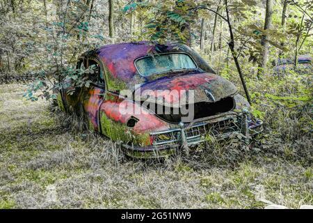 Viejo coche oxidado abandonado en el bosque
