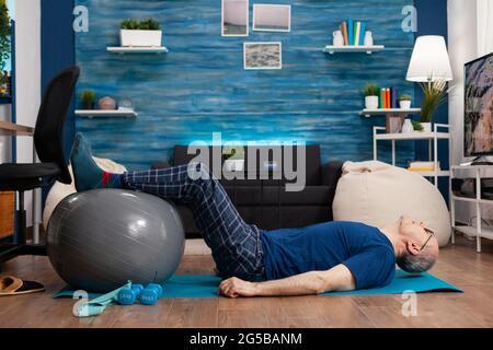 Deportista jubilado de edad sentado en una colchoneta de yoga practicando ejercicios de calentamiento de piernas usando una pelota suiza que estira los músculos abdominales. Entrenamiento de pensionistas centrado resistencia corporal en el salón