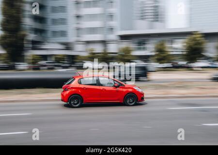 Ucrania, Kiev - 27 de junio de 2021: Red Peugeot 208 coche en movimiento en la calle. Editorial