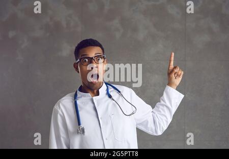 Un médico afroamericano conmocionado que apunta más fino arriba retrato del estudio de la cabeza