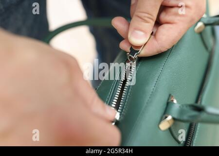 Las manos masculinas se tiran con cremallera hasta el primer plano de la bolsa de cuero verde