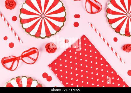 Parte plana con platos de papel, vasos en forma de corazón, rosas, confeti y pajas de beber sobre fondo rosa