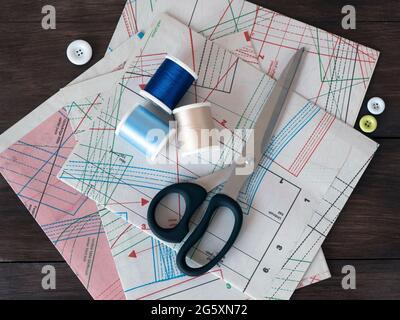 Hojas de dibujo para coser, tijeras de vendaje, carretes y botones sobre un fondo de madera oscura. Patrones de ropa profesional y artículos de costura