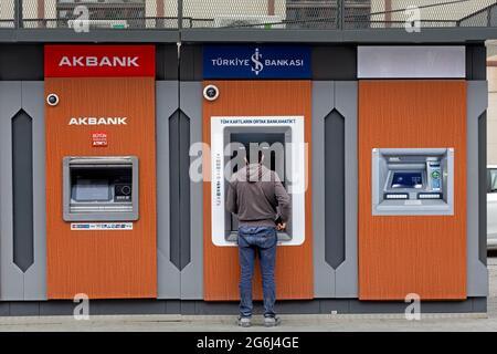 Hombre con vestido casual delante de Akbank, banco Isbank ATM s, retirada de dinero. Karakoy, Estambul - Turquía.