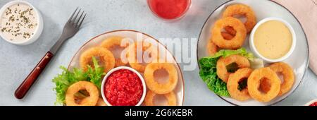 Panorama de los anillos de calamares. Anillos de calamar fritos profundos, platos de marisco con vino y diversas salsas, tiro plano superior