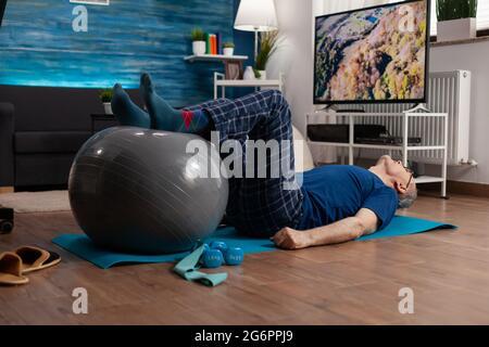 Jubilado hombre mayor haciendo bienestar calentar piernas con pelota suiza sentado en colchoneta de yoga en la sala de estar. Jubilado pensionista que practica ejercicios abdominales trabajando en la salud muscular del cuerpo