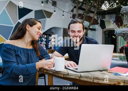 Dos jóvenes estudiantes hispanos que estudian juntos usando el ordenador portátil en la universidad de América Latina