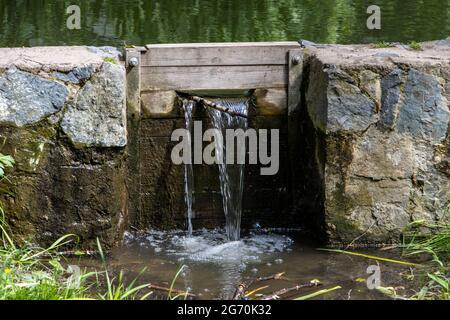 Un agua fluye a través de las esclusas en la pequeña presa de piedra del estanque