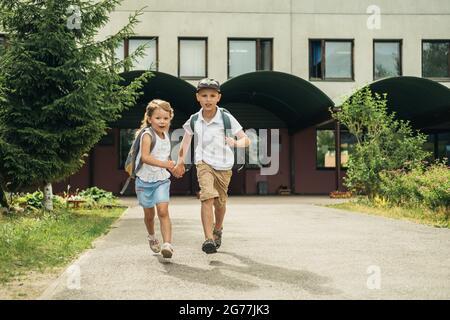 Dos niños caucásicos, niño y niña, corriendo de la escuela con bolsas detrás de sus espaldas y libros. Regreso a la escuela.