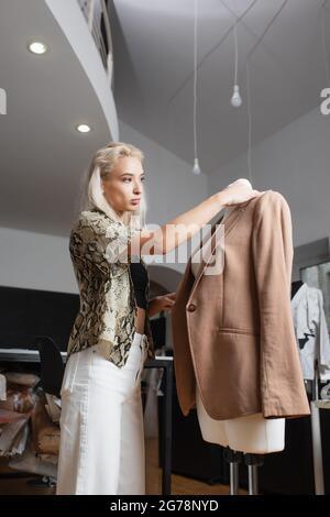 elegante diseñador de moda situado cerca de blazer en el maniquí