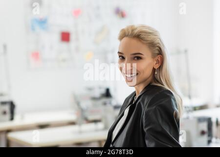alegre, moderno diseñador de moda sonriendo en la cámara en la tienda de sastre