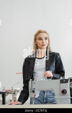 joven diseñador de moda mirando lejos cerca de la máquina de coser