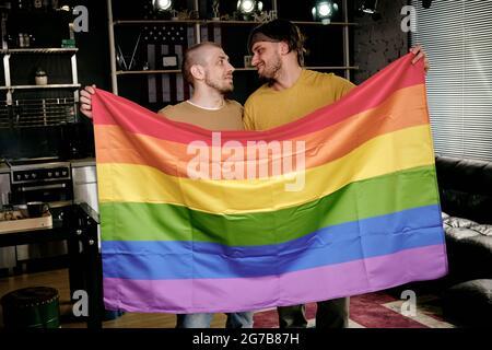 Jóvenes hombres homosexuales afectuosos sosteniendo la bandera del arco iris y mirando unos a otros cuando están de pie en el apartamento
