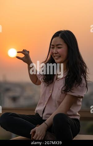 La mujer tailandesa china asiática juega con la forma del sol en la azotea en el crepúsculo.