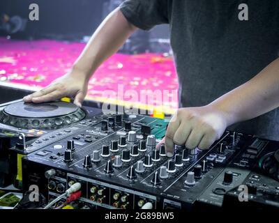 Disc Jokey le da la mano a una estación mezcladora de sonido y al vinilo en el club nocturno en una fiesta. Vida nocturna en el club, concepto de fiesta