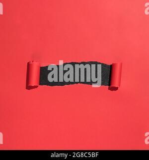 El papel rojo se ha abierto en papel rasgado para revelar el espacio de copia en negro