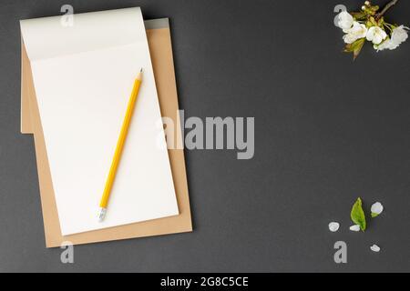 Cuaderno marrón con lápiz amarillo.