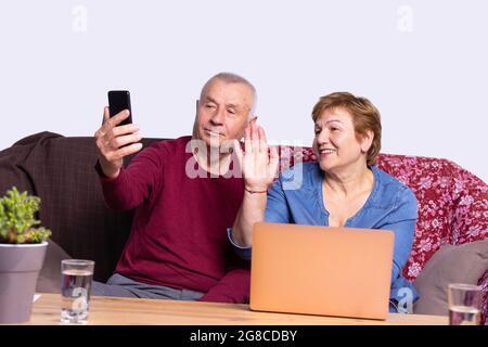 Marido y mujer están sentados delante de la computadora con dos vasos de agua en la mesa y hablando en línea en el teléfono móvil. Fotografías de alta calidad