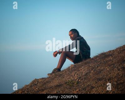 Uribia, La Guajira, Colombia - 28 2021 de mayo: Joven hombre latino marrón con los bráidos en su cabeza se sienta penosamente esperando la puesta de sol en el desierto
