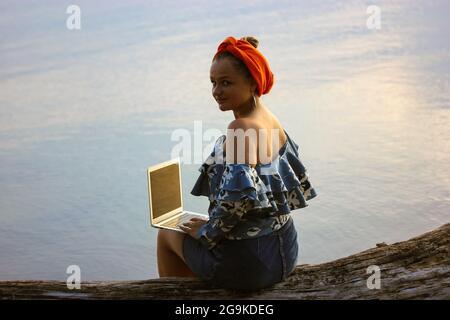 Una joven y hermosa empresaria musulmana malaya con un turbante de hijab naranja en la cabeza, trabajando en un portátil sentado junto al mar en un día de verano. Trabajo remoto, l