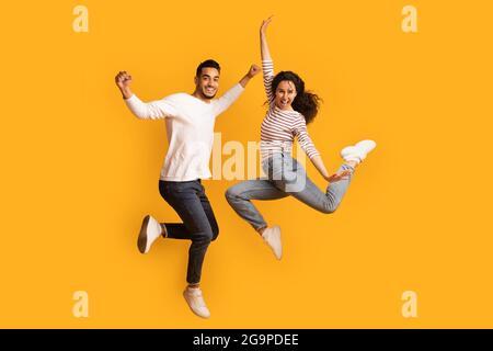 Ventas increíbles. La pareja árabe sobregozada salta en el aire con las manos levantadas