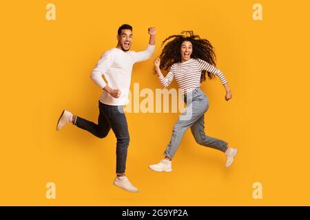 Emocionado overjoyed Arab Couple Jumping en el aire sobre fondo amarillo