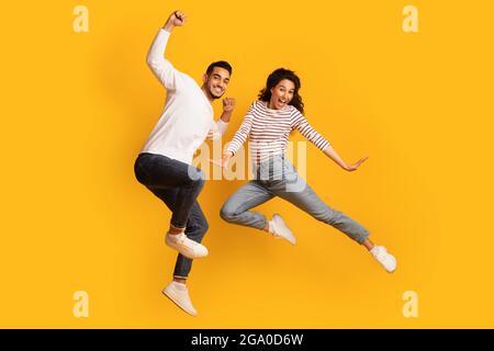 Diversión loca. Alegre y excitada pareja de Oriente Medio Jumping en aire sobre fondo amarillo