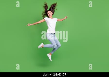 Foto larga de loco morena millennial dama salto vestir camiseta jeans aislados sobre fondo de color verde