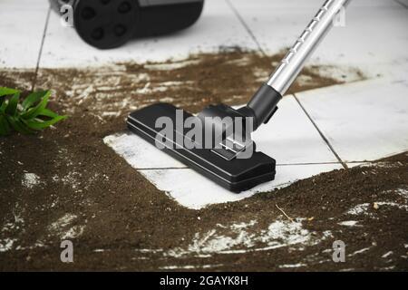 Limpieza al vacío después de caer la maceta de flores en un suelo de baldosas