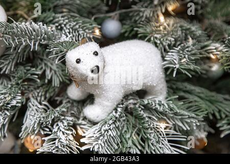 Foto de oso de peluche blanco sentado en el árbol de Navidad en la nieve, decoración del árbol de Navidad, concepto festivo, luces